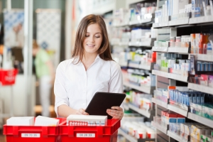 Pharmacist using a digital tablet while filling prescriptions