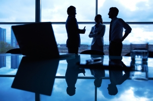 Three office workers interacting by the window with their workplace in front
